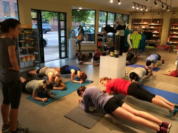 Runners doing planks during core training after the group run