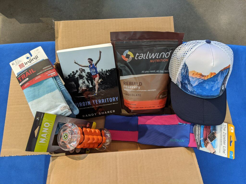 A box full of Run Hub products, including hats, nutrition, and books